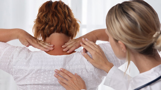 Woman suffering from back pain during medical exam