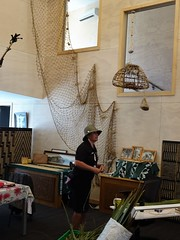 Rotorua. At Whakarewarewa Living Maori Village  in the womans weaving school a Maori woman explains the use of flax leaves in traditional weaving.