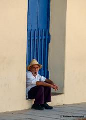 Cuban Man sitting in a doorway, smoking a cigar, Trinidad, Cuba