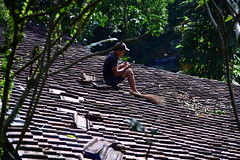 One of the work men fixing roof tiles on a building catches up on his texting!