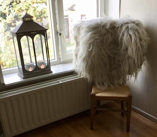 Houten stoel met schapenvacht windlicht
