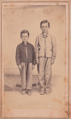 Portrait of two boys being held still by posing stands (1860s)