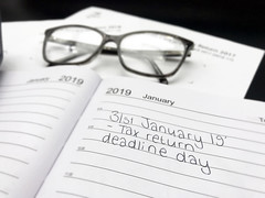 Tax return deadline day 2018, amid tax return forms, glasses and a calculator