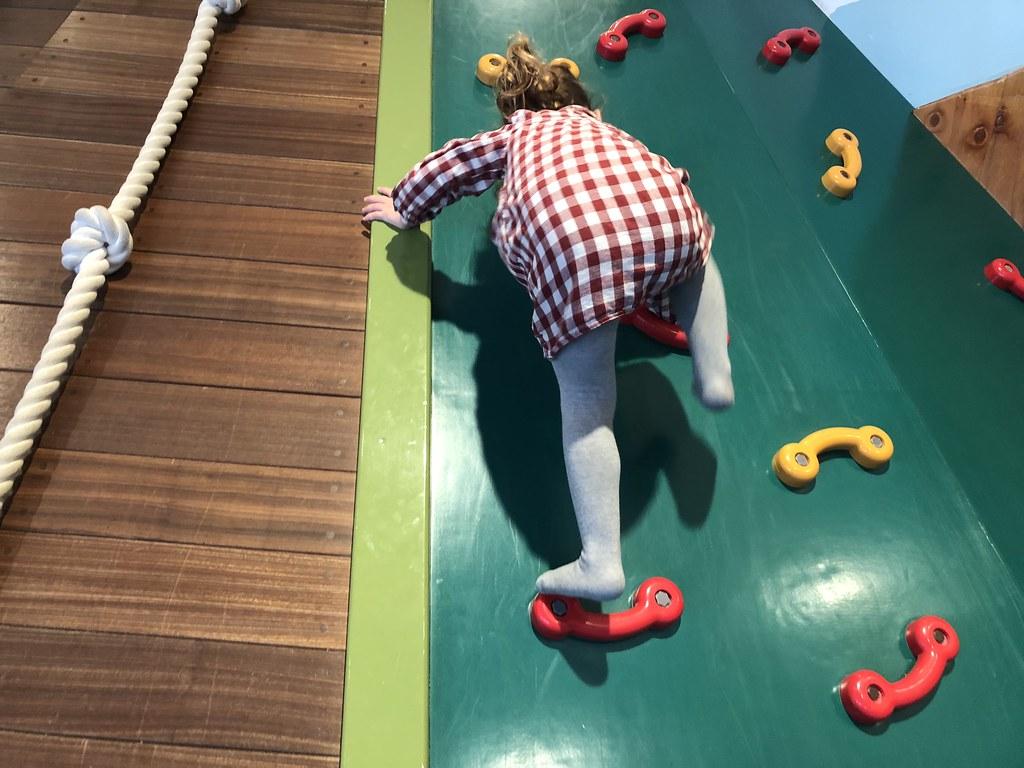 Escalando para tirarse por uno de los toboganes a la piscina de bolas