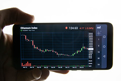 Hand holding smart phone with Ethereum chart on screen