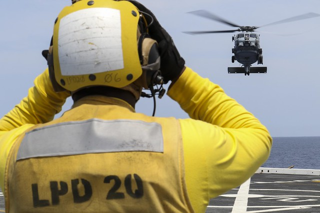 CORAL SEA (Nov. 19, 2018) Aviation Boatswain's Mate (Handling) 3rd Class Dion Sanders, from New York, signals a MH-60R Seahawk helicopter, assigned to the Royal Australian Navy helicopter landing dock ship HMAS Adelaide (L01), as it lands on the flight deck of the amphibious transport dock ship USS Green Bay (LPD 20) during cross deck flight operations. Green Bay, part of Commander Amphibious Squadron 11, is operating in the region to enhance interoperability with partners and serve as a ready-response force for any type of contingency. (U.S. Navy photo by Mass Communication Specialist 2nd Class Anaid Banuelos Rodriguez)