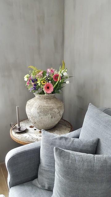 Grijze bank wijntafel kruik met bloemen
