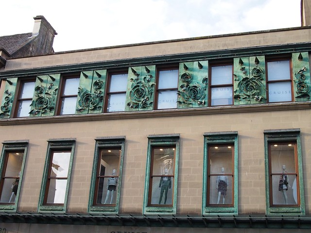 Building with a row of first floor display windows with shop mannequins. Above is a row of smaller windows alternating with greenish copper-coloured rose shapes and conical spikes.