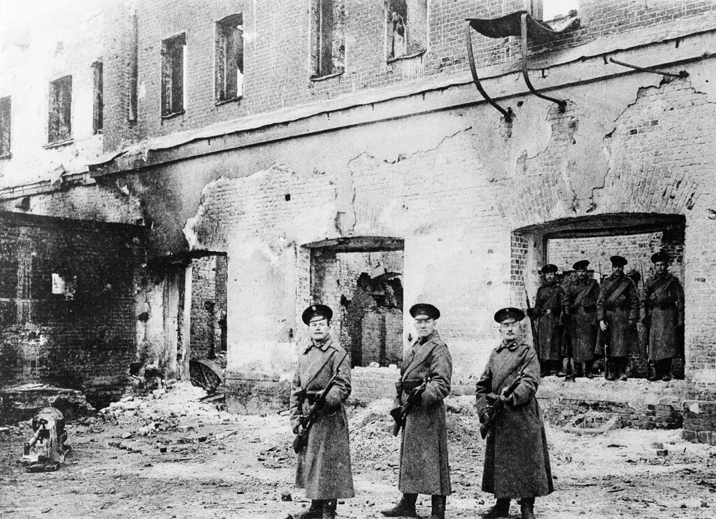 Солдаты с пристёгнутыми штыками перед разрушенным зданием завода. Декабрь