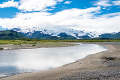 Katmai National Park with river, beach, sand and mountains with glaciers. Sunny summer day in Alaska