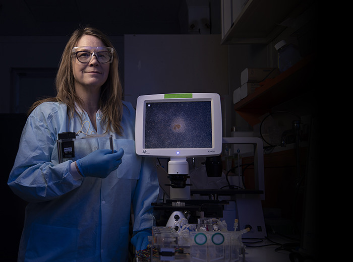 A women in a lab coat, safety glasses, and gloves stands next to a medical device.