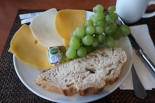 Weintrauben und verschiedene Käse zu Weißbrot mit Butter