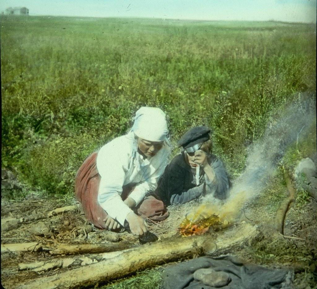 Мать с сыном жарят картошку в поле