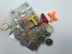 Magnetic letters spell out the word 'tax', accompanied by various sterling coins and notes