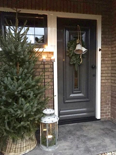 Kerstboom en kaarslicht bij de voordeur