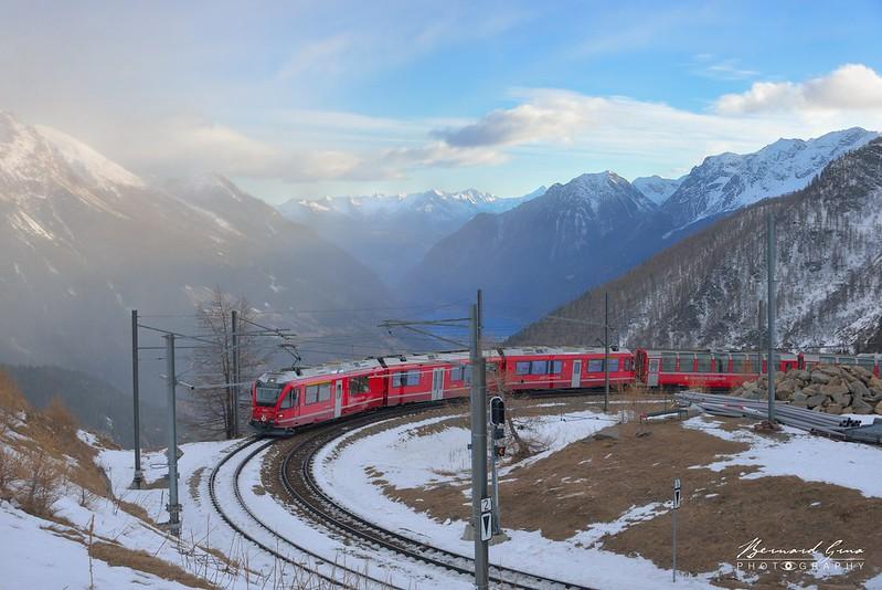 Courbe au niveau de la gare de l'Alp Grüm, altitude 2 091 m, au dessus du Valposchiavo et de son lac. Au fond, les Alpes Bergamaises. ,  Bernina Express, par  Bernard Grua - Rhätische Bahn, Chemins de fer rhétiques