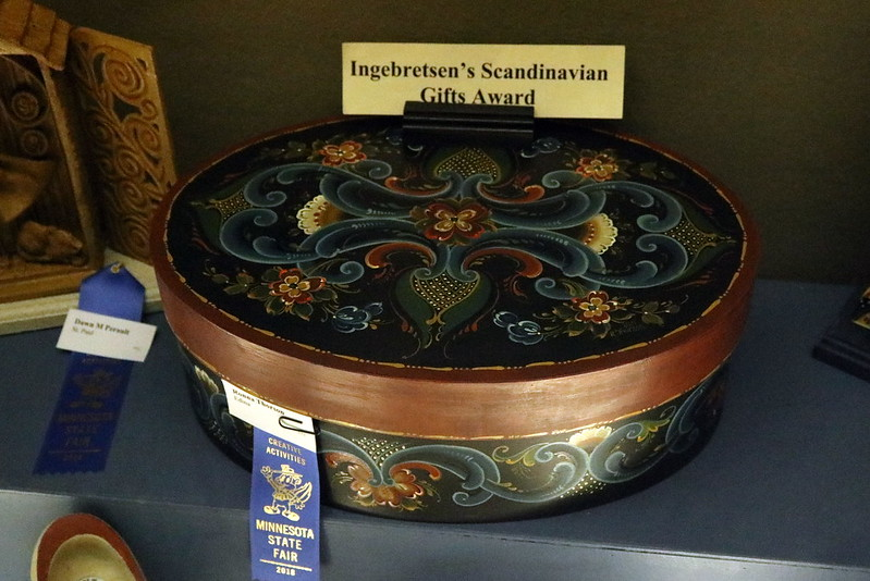 A blue ribbon-winning oval basket with lid, decorated with dark swirls and flowers.