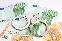 Metallic police handcuffs on euro banknotes