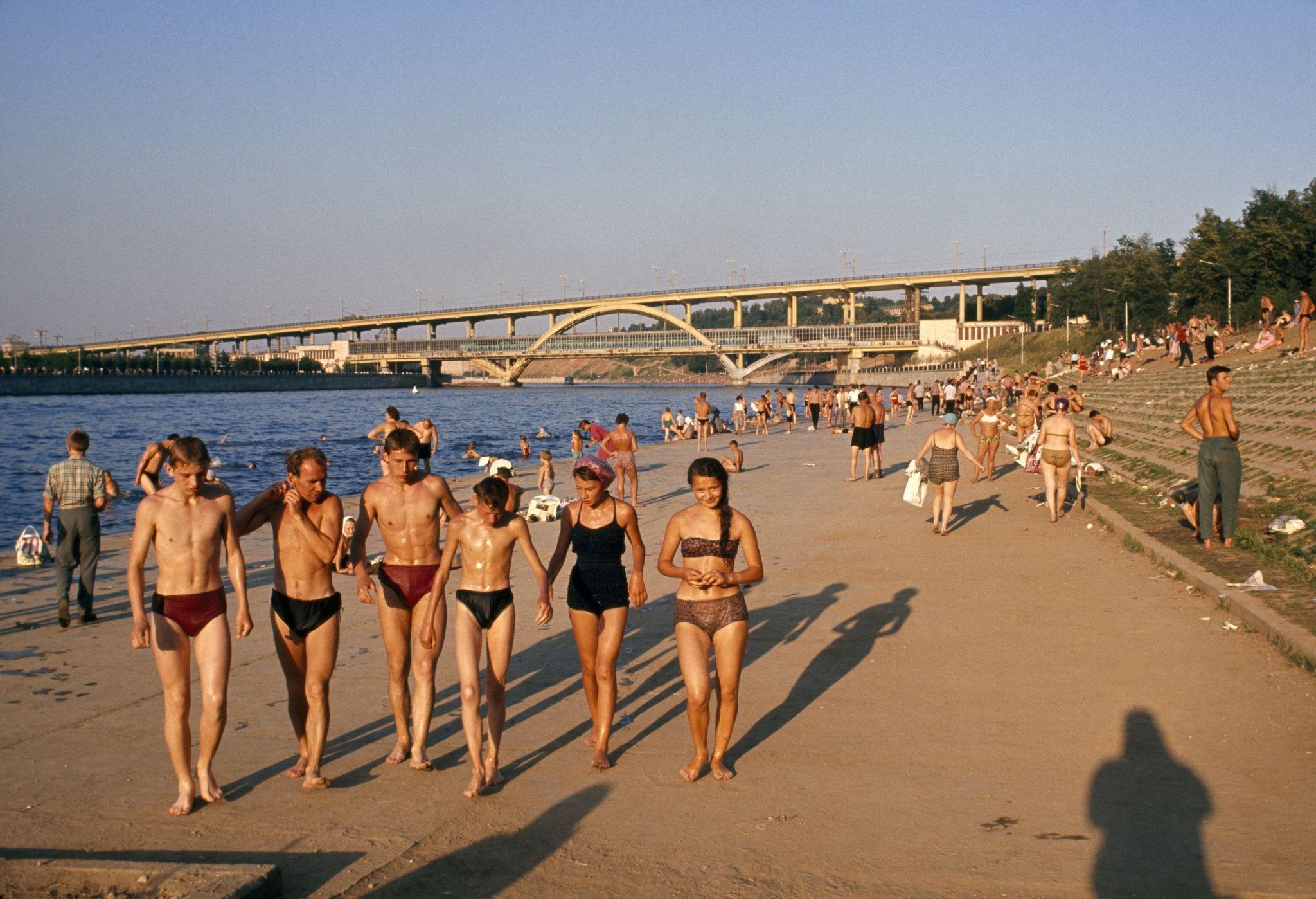 1964. Купальщики гуляют по многолюдному берегу реки возле моста