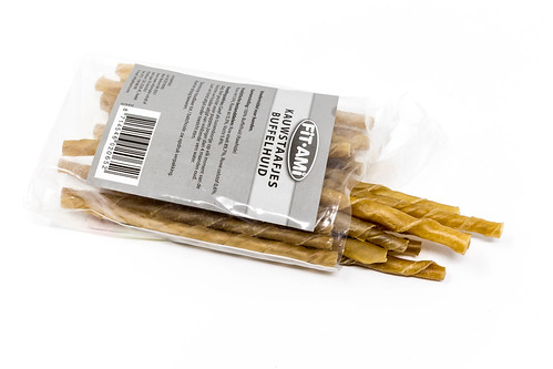 Chewing sticks for dogs made of buffalo skin in plastic bag against white background