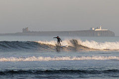 Surfer with the Farne Islands as a backdrop.