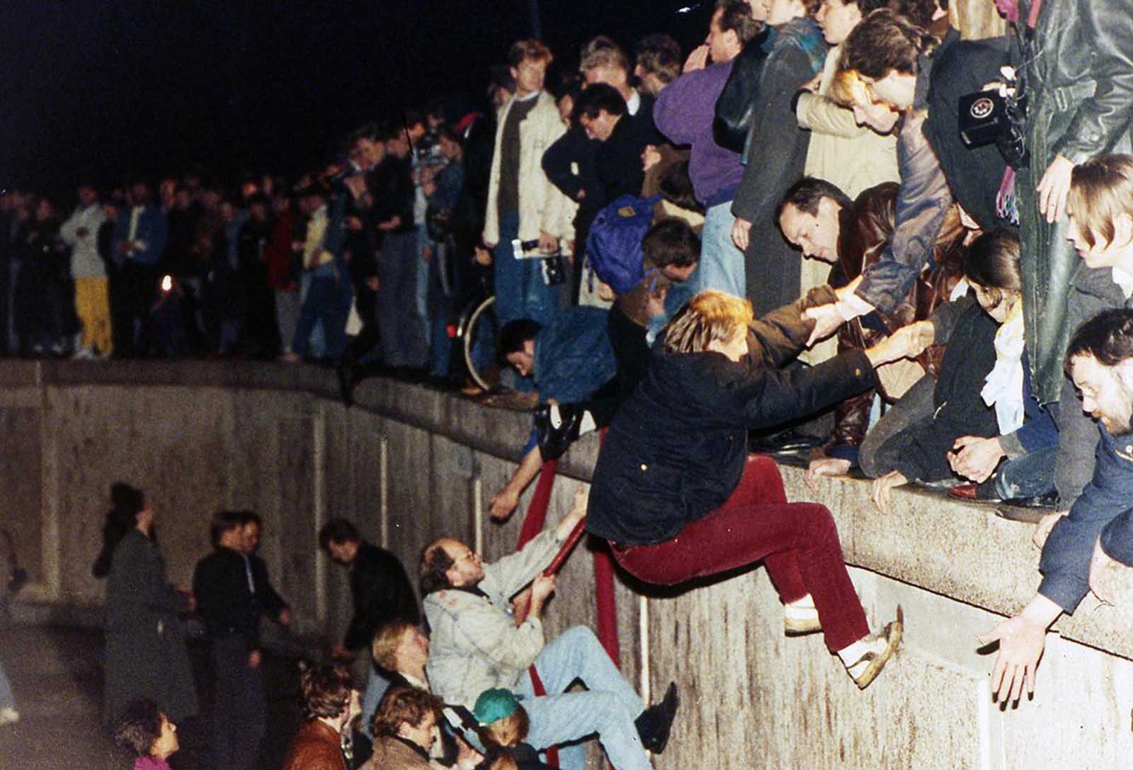 East Berliners get helping hands from West Berliners as they climb the Berlin Wall which divided the city for decades, near the Brandenburger Tor (Brandenburg Gate). Photo taken in the early hours of November 10, 1989.