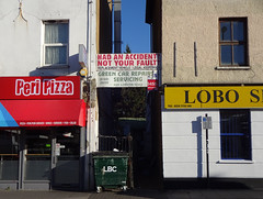 "A narrow alleyway between two buildings with ground-floor shopfronts reading ""Peri Pizza"" on the left and ""Lobo"" on the right.  A large dark green commercial bin with ""LBC"" in white lettering is in front of the alleyway.  A sign spanning the alleyway above head height reads: ""Had an accident?  Not your fault?  Replacement vehicle / legal assistance.  Green Car Repairs / Servicing / 200 London Road""."