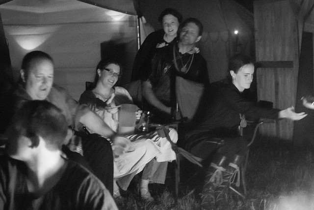 monochrome image of a group of people sitting in camp chairs near a fire