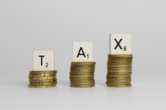 The word Tax written with wood blocks on top of coins piles