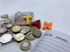 Magnetic letters spell out the word 'tax' accompanied with a 2019 diary and various sterling coins and notes