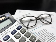 2 tax return forms, a 2018 tax return form and 2017 tax return form, black glasses and a calculator.