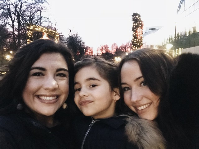Two women smiling with a child in the middle in front of trees covered in lights.