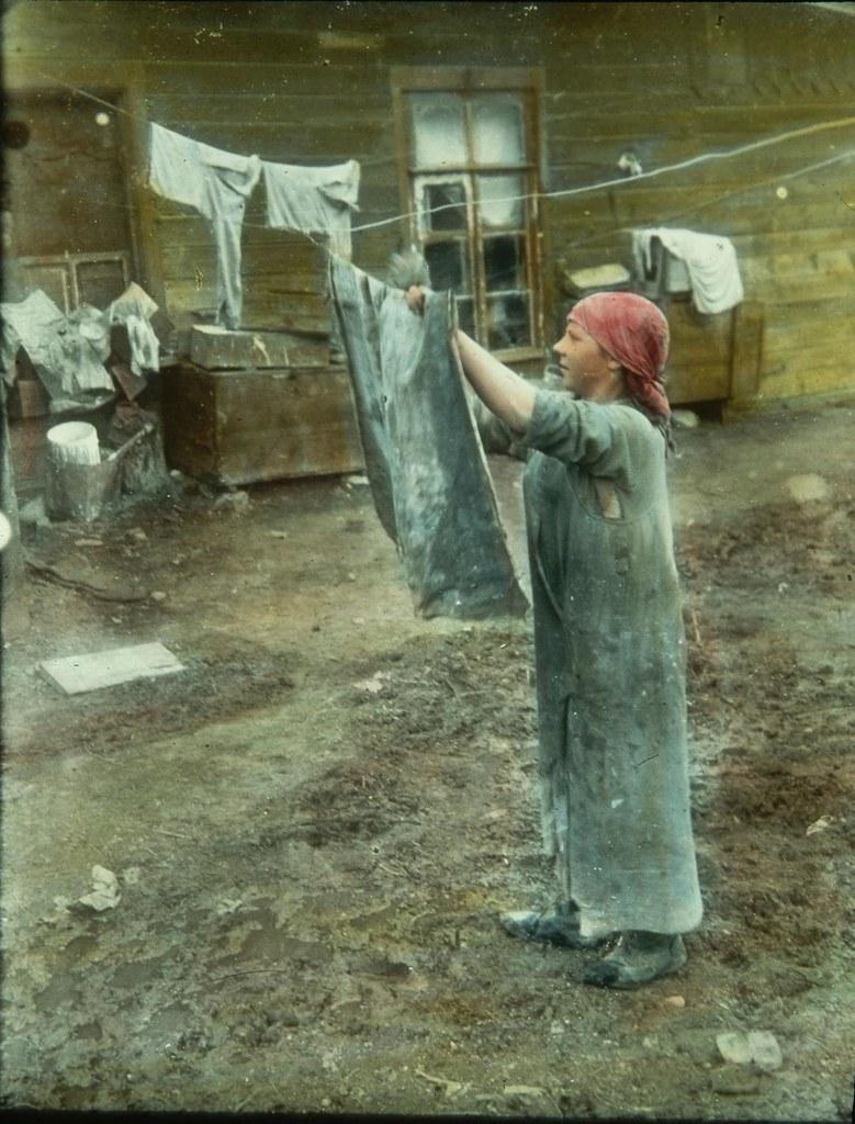 Молодая женщина вешает мокрое белье на бельевую веревку