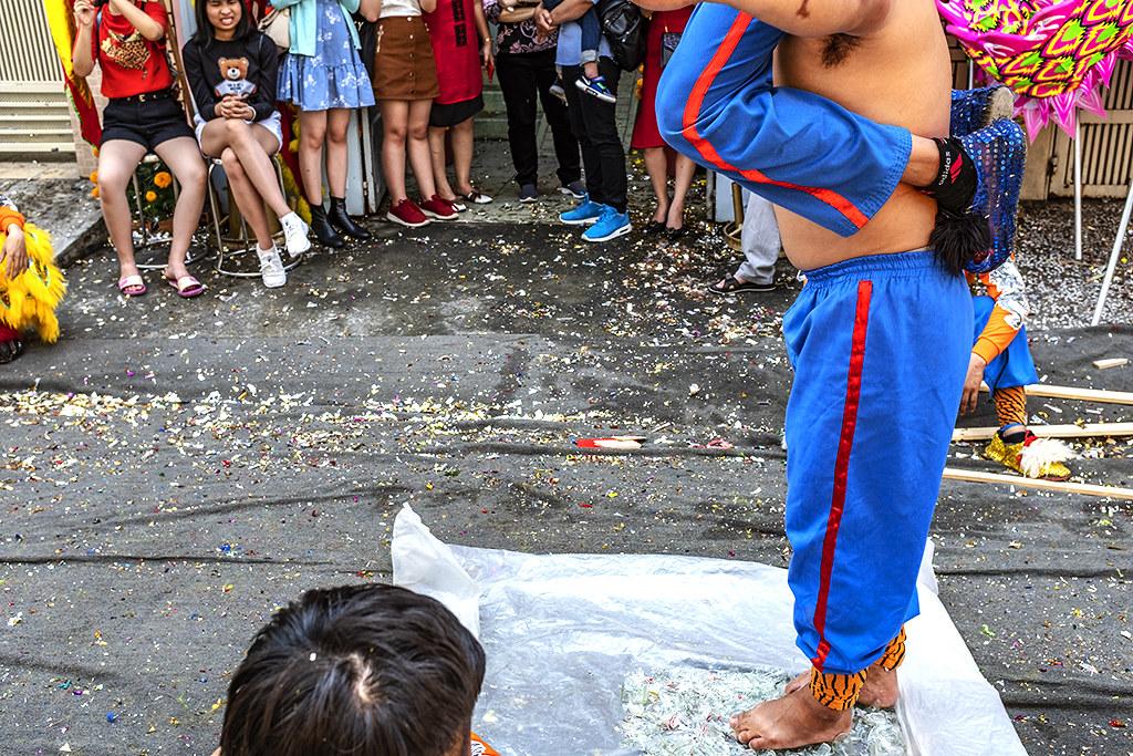 Man walks on broken glass while carrying another man--Saigon