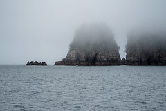 Large sea stacks in Kenai Fjords National Park with a lot of fog in the Resurrection Bay