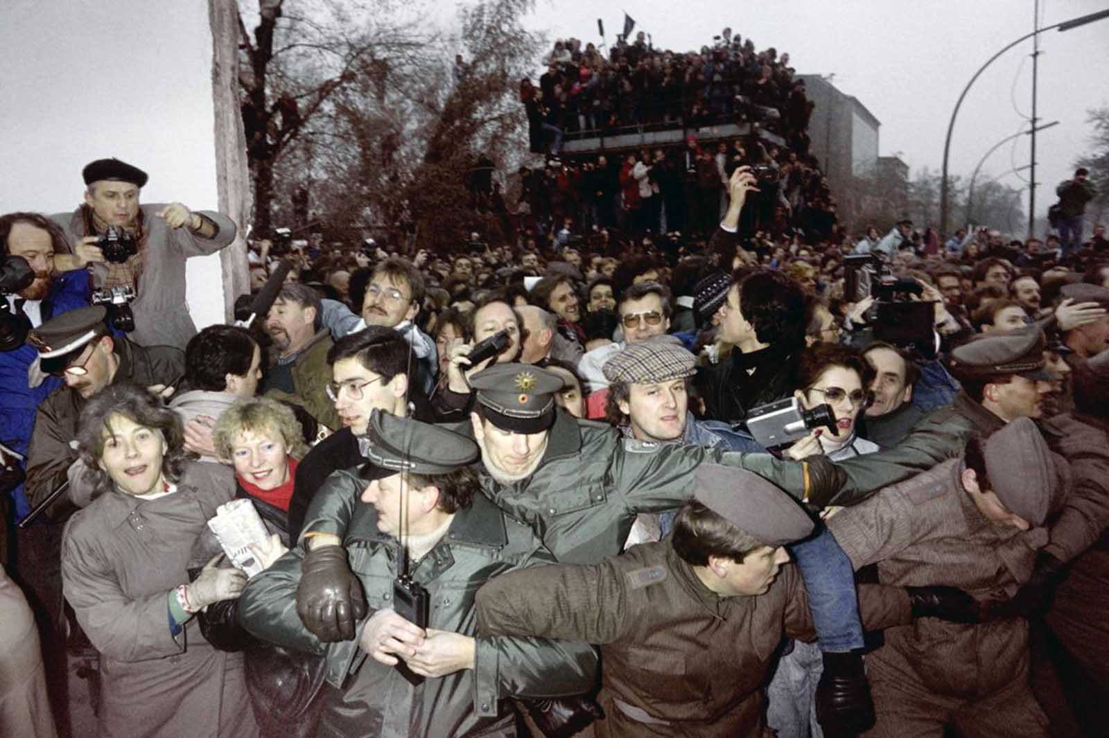 East and West German Police try to contain the crowd of East Berliners flowing through the recent opening made in the Berlin wall at Potsdamerplatz. Photo taken on November 12, 1989.