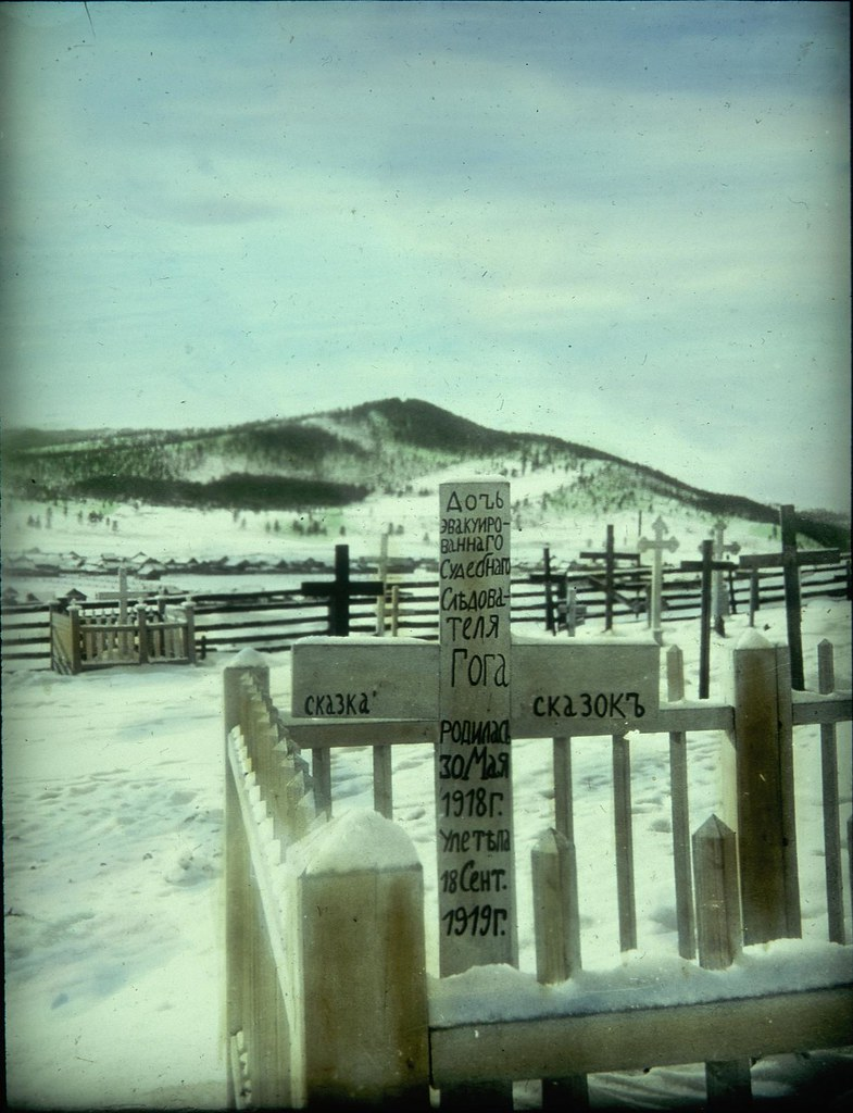 Крест на огороженной могиле на заснеженном кладбище.
