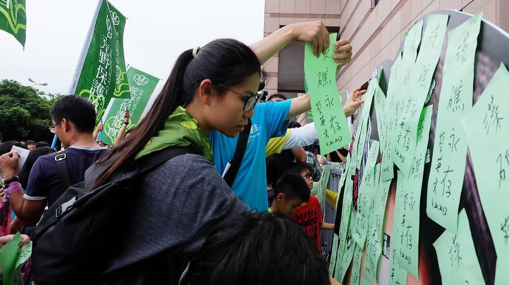 民進黨部前,遊行民眾貼上當初蔡英文承諾的「藻礁永存」字條。攝影:陳文姿