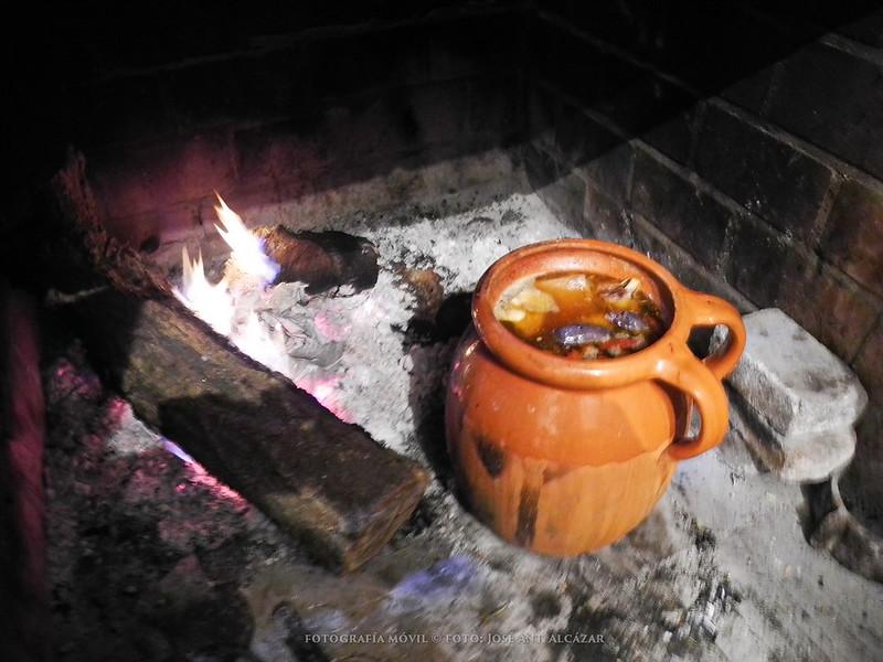 Puchero de barro en la lumbre, en el que se esta cocinando un potaje.