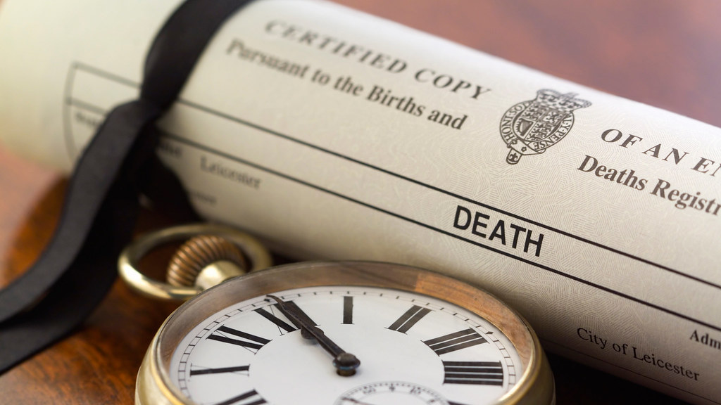 A death certificate next to a pocket watch