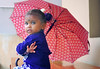 Indian baby girl under a large umbrella during the monsoon season