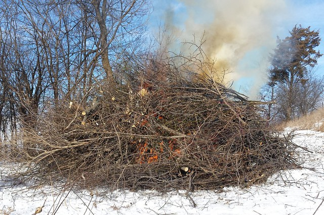 Large pile of sticks and branches, with some orange fire visible in the middle, and a plume of smoke at top right.