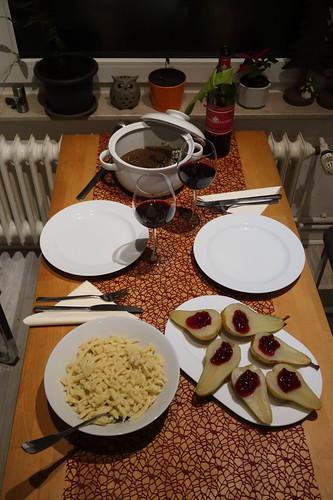 Hirschragout mit Spätzle und heißen Birnen mit Preiselbeeren (Tischbild)
