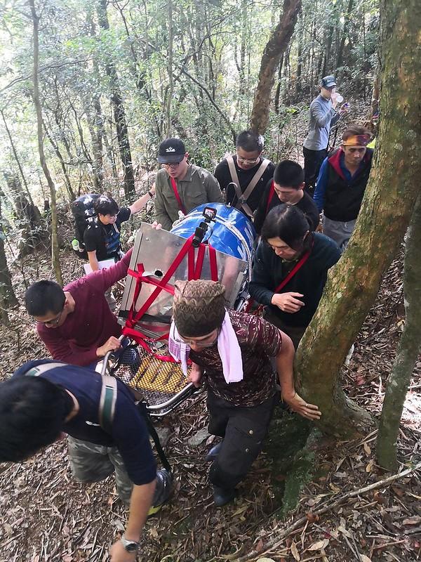 10月30日,由山林到車道需上爬百餘公尺,東勢林區管理處的森林護管員輪流將負有黑熊運輸桶的擔架扛上山。平日森林護管員即需要在林地內巡護、協助森林資源調查或緊急時協助救難,這還是第一次動員這麼多人力救援野生動物。(照片提供東勢林區管理處)