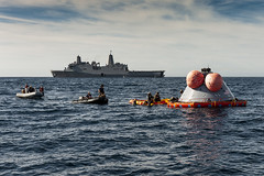 """U.S. Navy divers prepare to attach the """"front porch"""" to a test version of the Orion capsule as part of Underway Recovery Test 7. (NASA/Tony Gray)"""