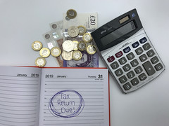 'Tax return due' note pictured on a 2019 diary page on the self assessment deadline day, 31st January 2019. Next to some coins and a calculator