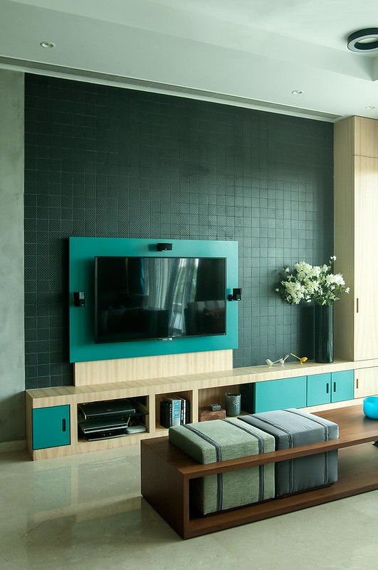 A teal / sea green backed TV unit in a modern living room in Mumbai.