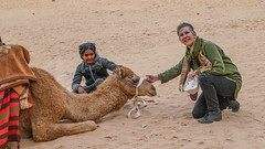 Tourist petting a dromedary near the Kharaz Rock Bridge