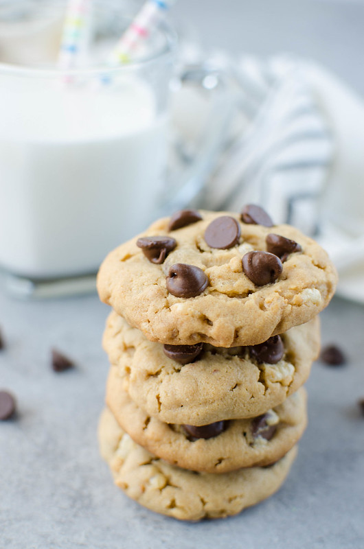 Stack of 4 peanut butter chocolate chip cookies with a glass of milk in the background