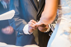 Groom inserting a ring to the Bride's finger